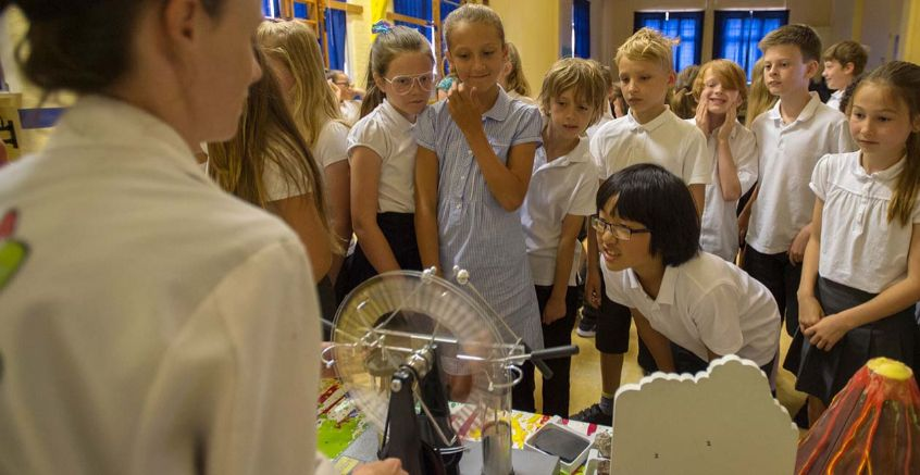 Kids gathered around a desk while the mad scientist shows them a whimehurst machine