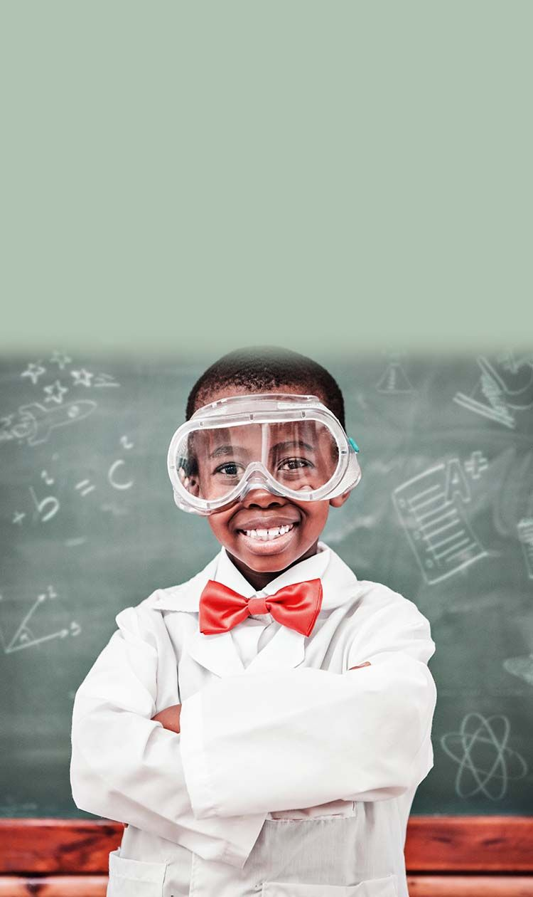 Boy wearing lab coat, red bow tie and safety goggles in a classroom.  Blackboard in the background with different science ico