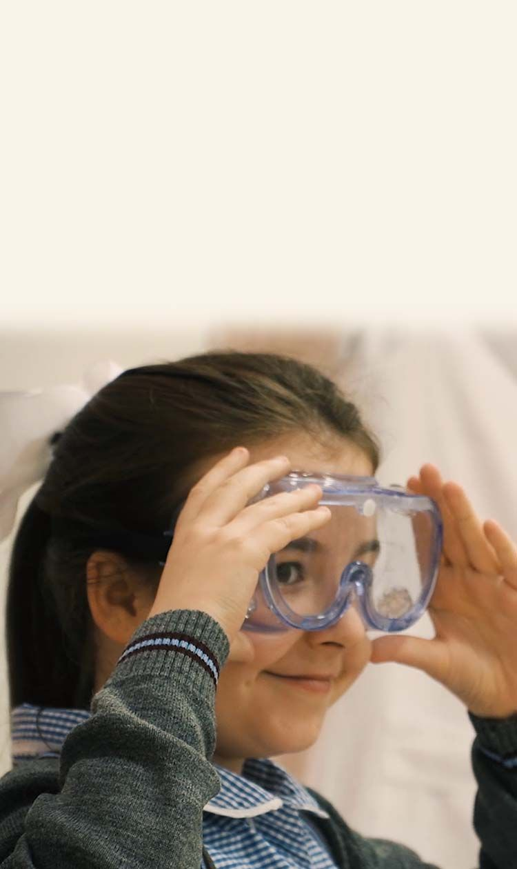 Girl smiling while wearing safety goggles
